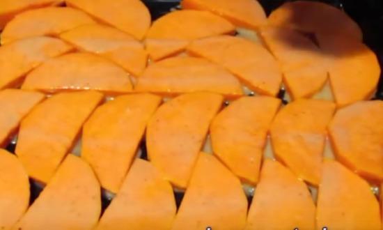 выкладываем тыквенные кусочки на противень и заливаем сметанный соусом