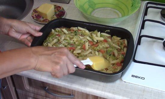 Выкладываем первым слоем фарш, а затем макароны с овощами